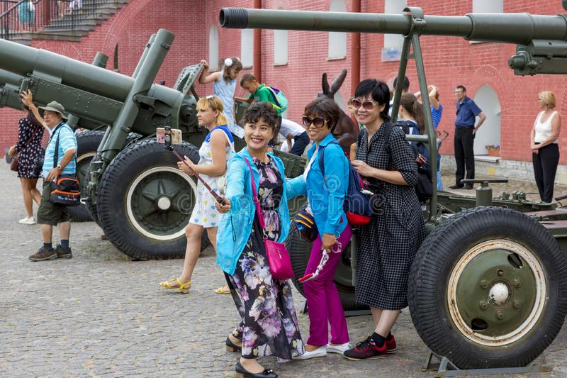 Tourists take pictures near the museum exhibits on the territory of the Peter and Paul Fortress in St. Petersburg stock image
