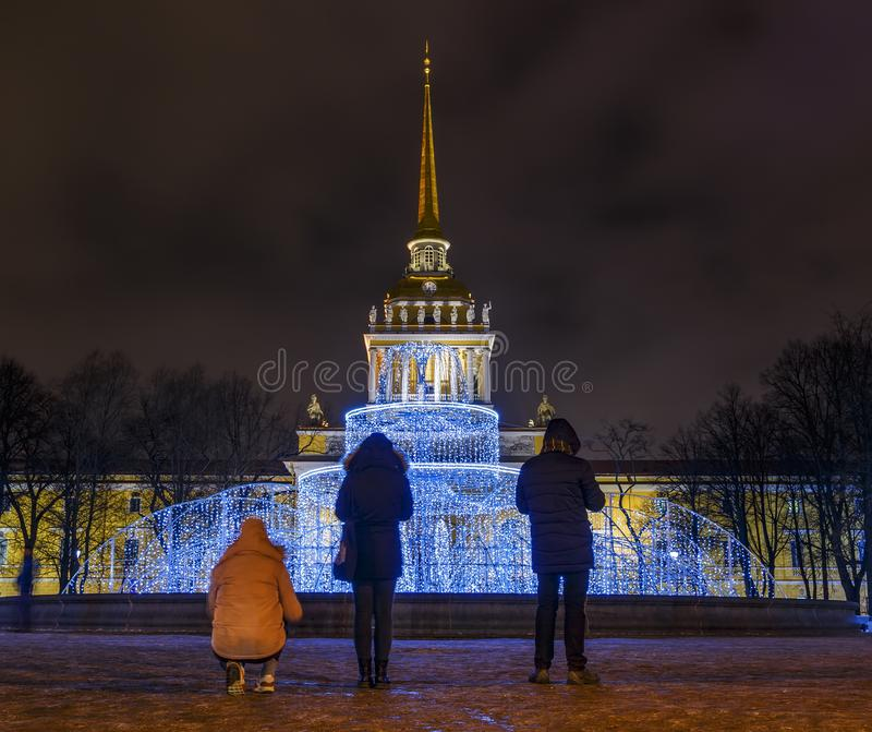 Tourists take pictures of the night city and fountain with lighting. Spire of Admiralty, St. Petersburg, Russia stock image