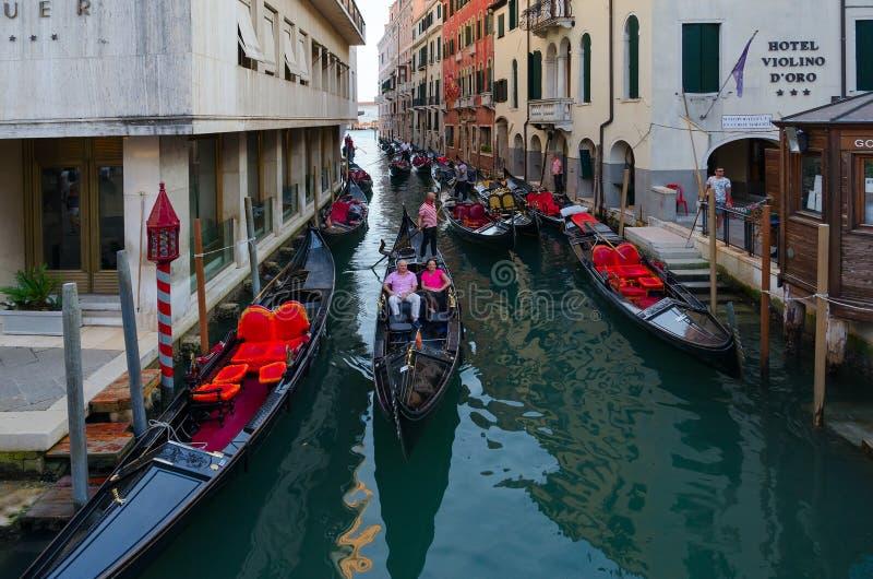 Tourists take walk on gondolas along canals of Venice, Italy stock photos