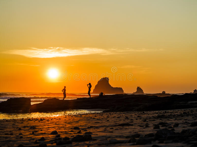 Tourists taking beach pictures at sunset royalty free stock photo