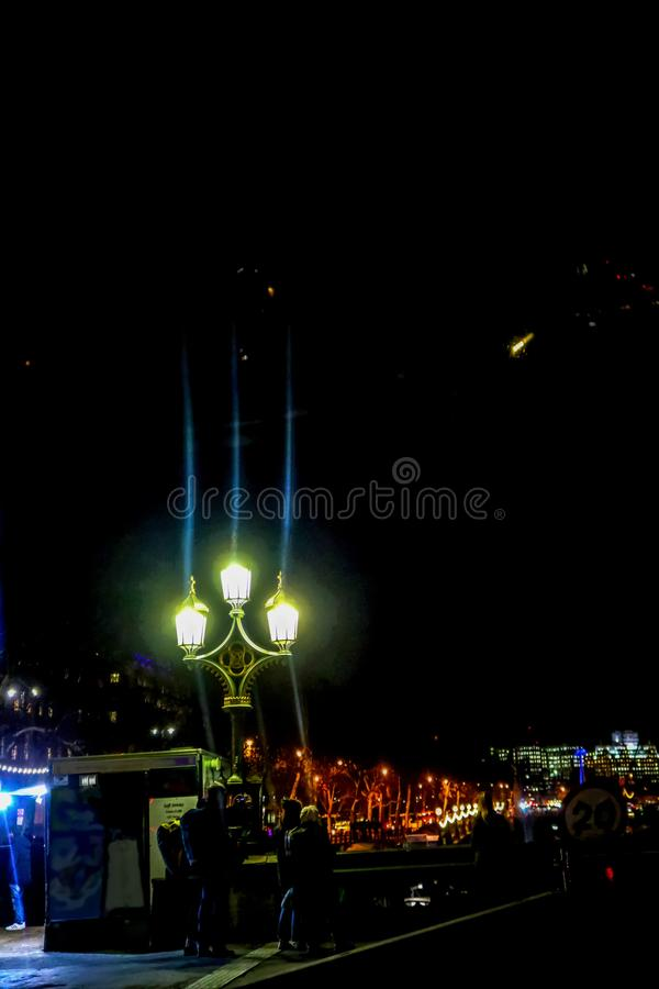 Tourists taking phone pictures of scene in London at night in the wintertime - entering Westminster Bridge from South bank - stock photos