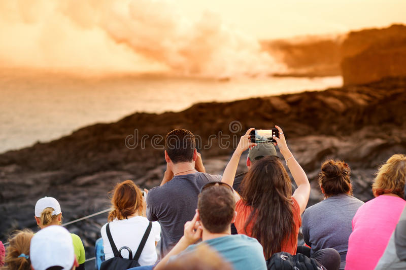 Tourists taking photos at Kalapana lava viewing area. Lava pouring into the ocean creating a huge poisonous plume of smoke at Hawa royalty free stock images