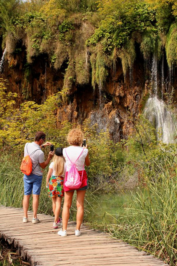 Tourists taking pictures of a waterfall at Plitvice Lakes National Park royalty free stock photos