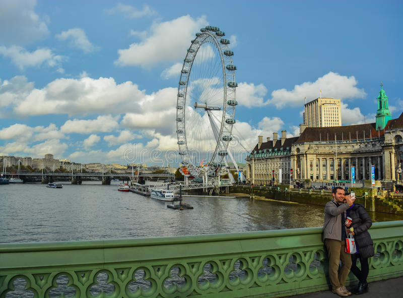 Tourists taking selfie in front of River Thames. A picture of tourists taking a selfie on Westminster Bridge with a London backdrop, including London Eye stock photos