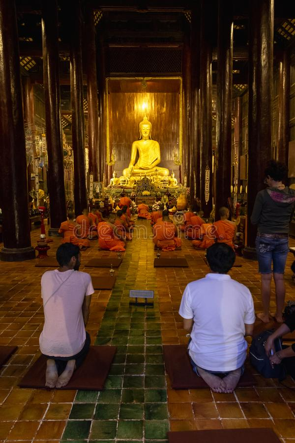 Tourists in a temple listening to monks chant in Chiang Mai stock images