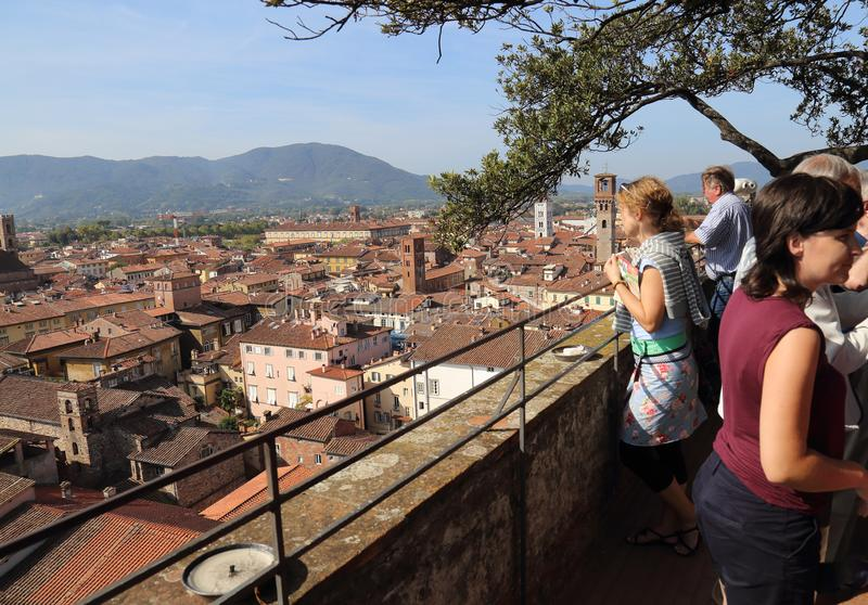 Tourists on a tower admire the view of Lucca, Italy. Lucca, Italy - September 28, 2017: Tourists admire the view from the Torre Guinigi tower in Tuscany in Lucca stock photos