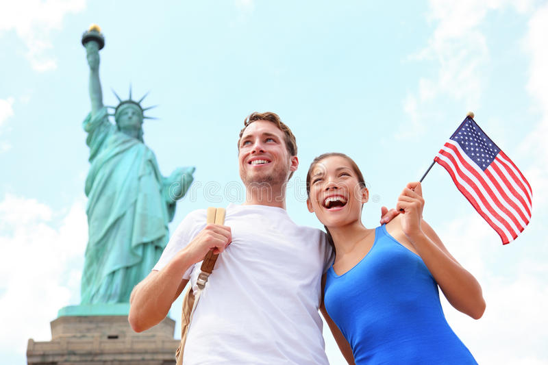 Tourists travel couple at Statue of Liberty, USA. Tourist travel couple at Statue of Liberty, New York City, USA. Multiracial tourist couple on summer vacation royalty free stock photography