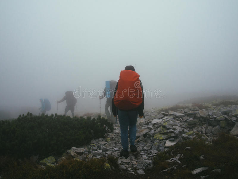 Tourists travelers with backpacks walking through the rocks in thick mist of milk. royalty free stock photography