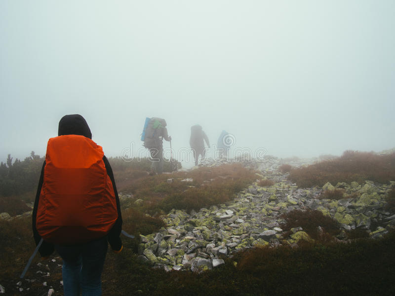 Tourists travelers with backpacks walking through the rocks in thick mist of milk. royalty free stock image