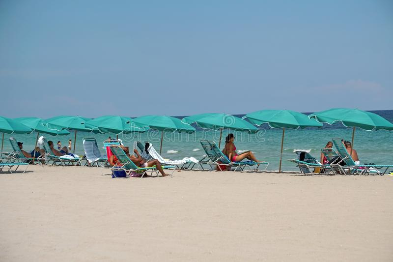 Tourists under beach umbrellas on Dania Beach stock photo