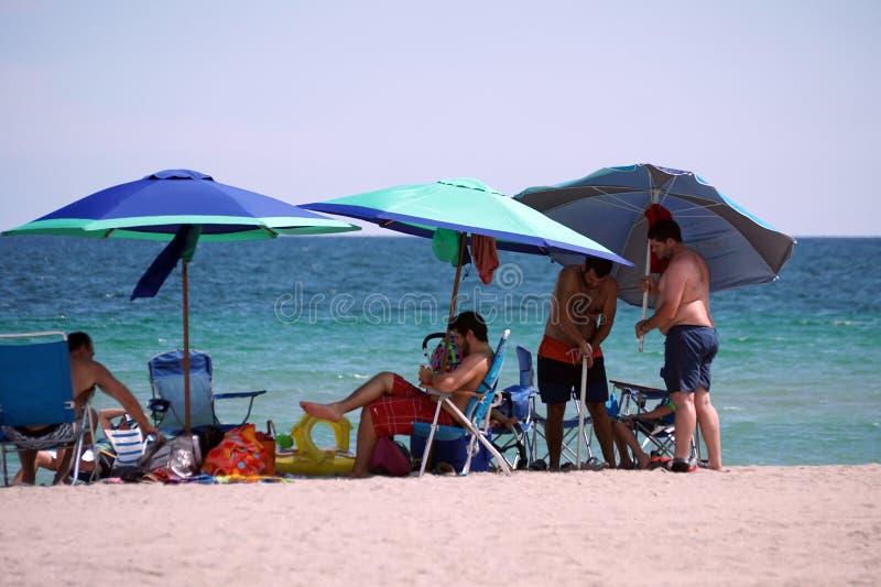 Tourists under colorful beach umbrellas on Dania Beach stock photo