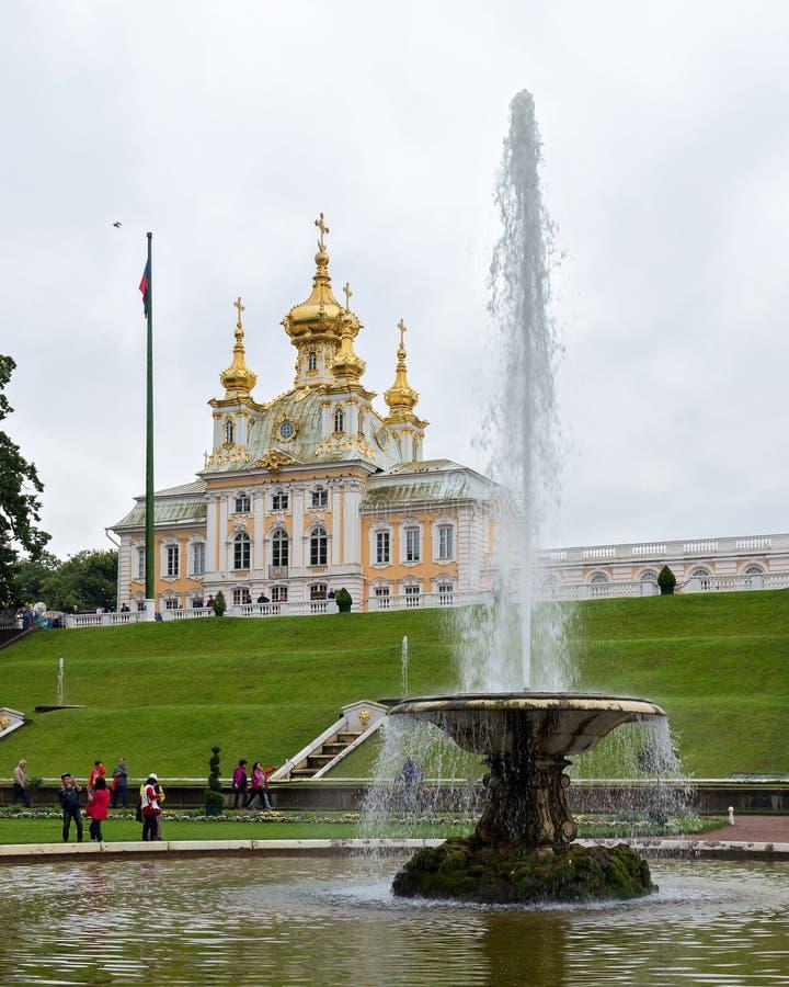 Tourists visit Peter and Paul Church and the fountain `Bowl`. Peterhof , Saint Petersburg, Russia stock photos