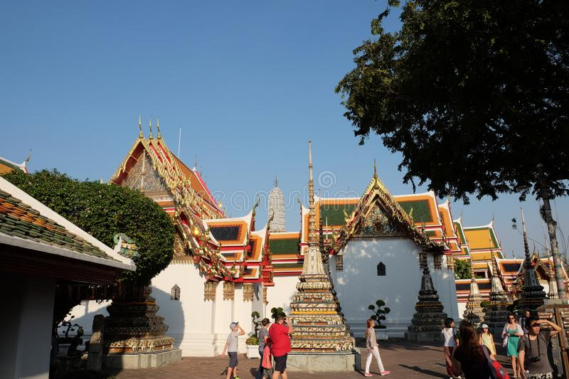Tourists visiting the beautiful buildings of the temple of Wat Pho. The courtyard of a stock photography