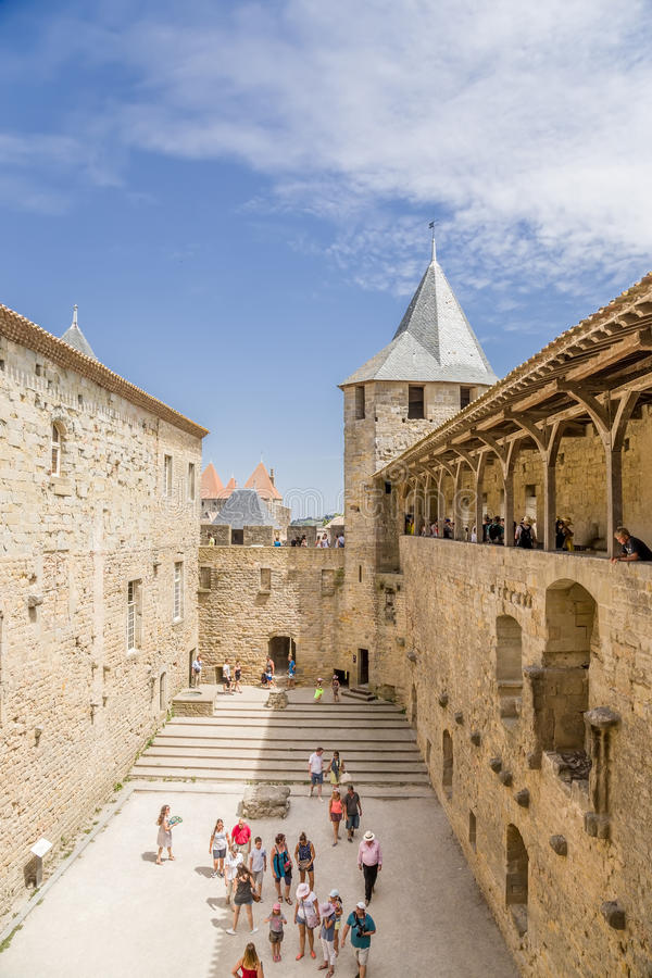Tourists visiting the courtyard of the castle Comtal in the fortress of Carcassonne (France), 1130. UNESCO List. Chateau Comtal is located within the fortress of royalty free stock image