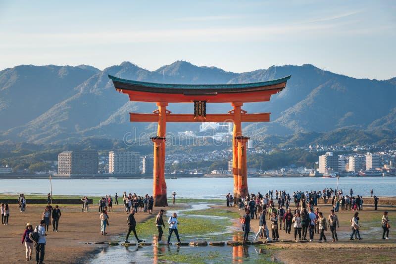 Tourists visiting the famous Torii Gate on Miyajima Island at low tide, Japan. Hiroshima, Japan - November 7, 2018: Tourists walk around the famous floating royalty free stock photos