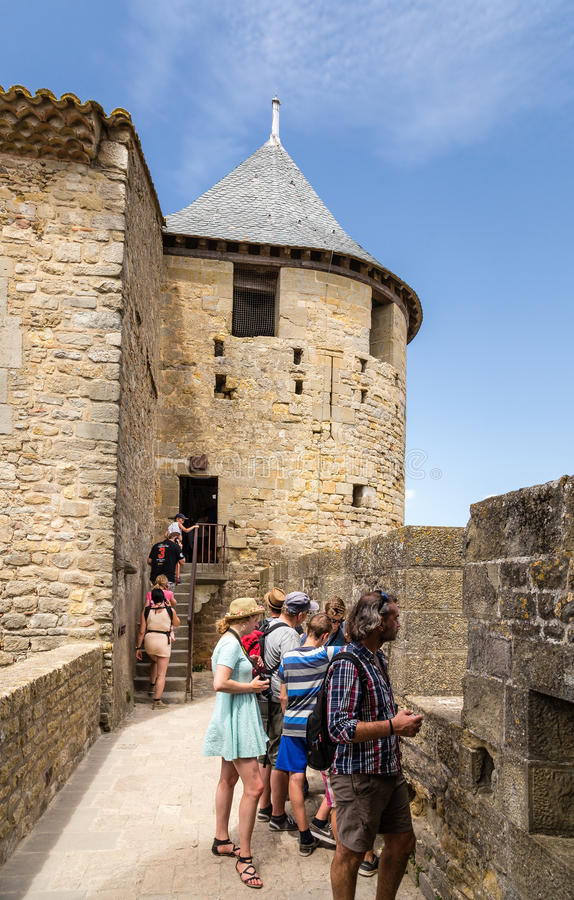 Tourists visiting the fortification of the castle Comtal in the fortress of Carcassonne (France), 1130. Chateau Comtal is located within the fortress of royalty free stock photo
