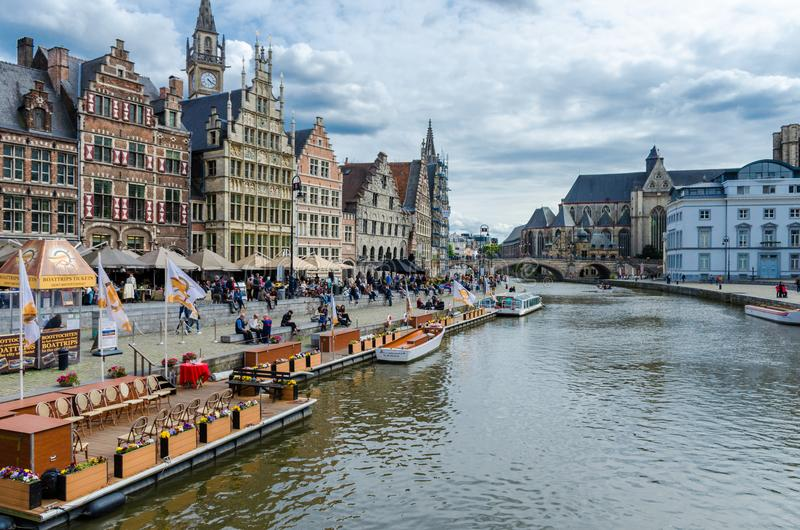 Tourists visiting historical center of Gent with medieval buildings overlooking the `Graslei harbor` on Leie river in Ghent town. GhentGent, Belgium - May 16 stock image