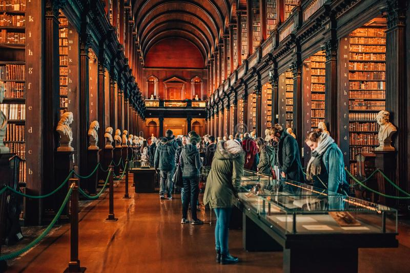 People visiting famous The Long Room in Old Library in Trinity College Dublin, Ireland. royalty free stock photography