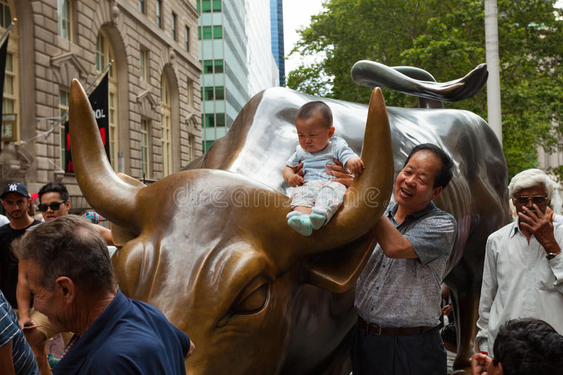 Tourists visits the Wall Street Charging Bull statue royalty free stock photography