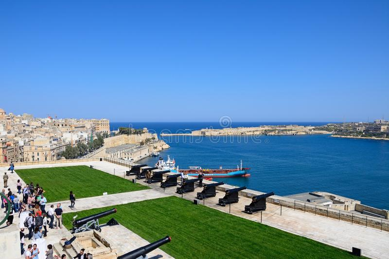 Tourists waiting for the Noon Gun,Valletta. Soldiers preparing the cannons ready for the Noon Gun in Upper Barrakka Gardens with views across the Grand Harbour stock photos
