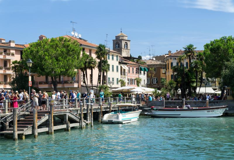 Tourists are waiting for a ship in the port of Sirmione on Lake Garda. stock photo