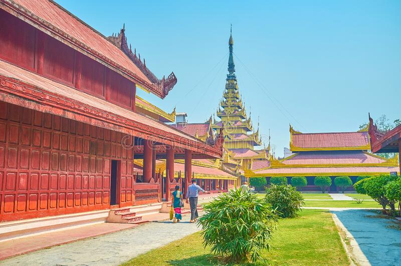 Lazy walk on the courtyard of the Royal Palace in Mandalay, Myanmar. The tourists walk along The Chief Queens Apartments of the Royal Palace and enjoy the beauty stock image