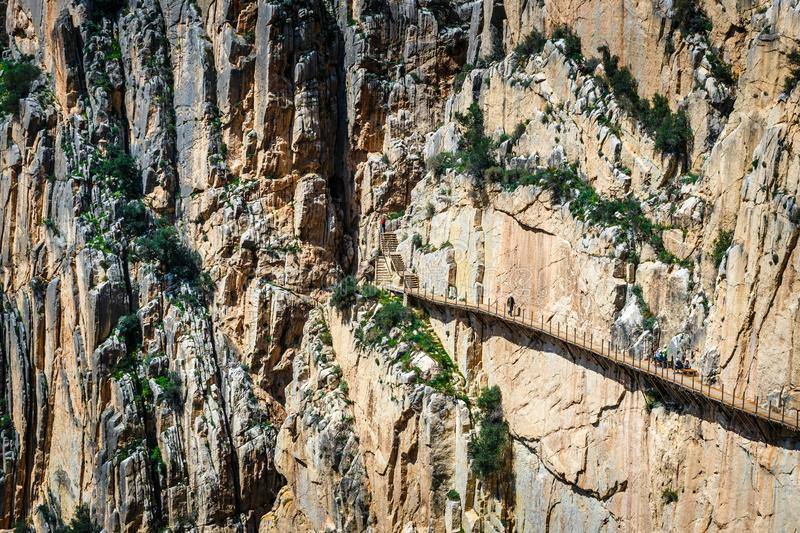 Tourists walk along the El Caminito del Rey, Malaga, Spain. Caminito Del Rey - mountain path along steep cliffs in Andalusia, Spain royalty free stock images