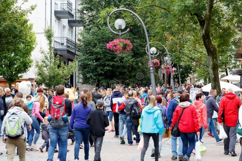 Tourists walk along Krupowki Street. Zakopane, Poland - August 07, 2017: Tourists walk along Krupowki Street during the holiday season. Countless number of royalty free stock image