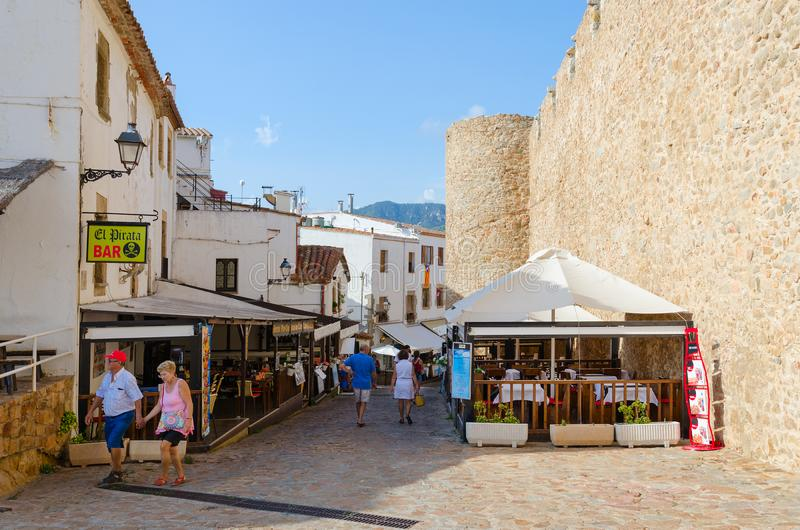 Tourists walk along narrow street in historic center of resort town of Tossa de Mar, Costa Brava, Catalonia, Spain royalty free stock photos