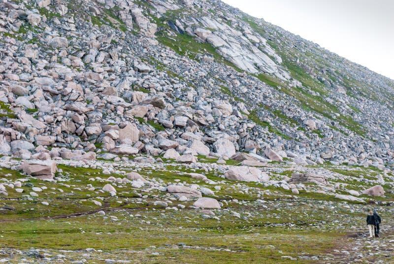 Tourists walk along the rocky slope, island of Mageroya, Norway. Tourists walk along the rocky slope, Mageroya island, Norway royalty free stock photo