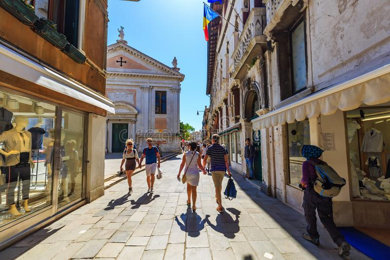 Tourists walk along the street in Venice. VENEZIA, ITALY - 20 APRIL 2018 - Unidentified tourists walk along the street under sunlight of midday in Venezia Venice royalty free stock images