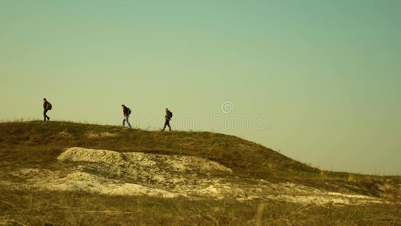 Tourists walk along the top of the hill. joint work of business people. The team of travelers goes to victory and. Tourists walk along the top of hill. joint royalty free stock photos