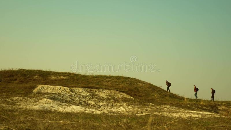 Tourists walk along the top of the hill. joint work of business people. The team of travelers goes to victory and. Tourists walk along the top of hill. joint stock image