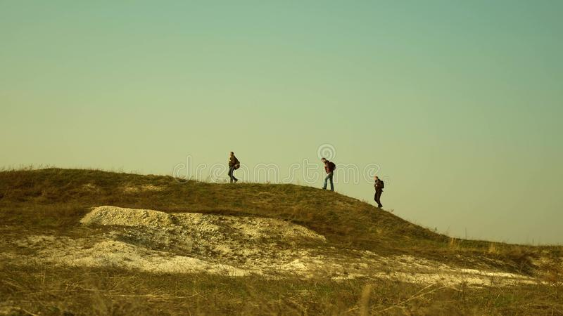 Tourists walk along the top of the hill. joint work of business people. The team of travelers goes to victory and. Tourists walk along the top of hill. joint royalty free stock image