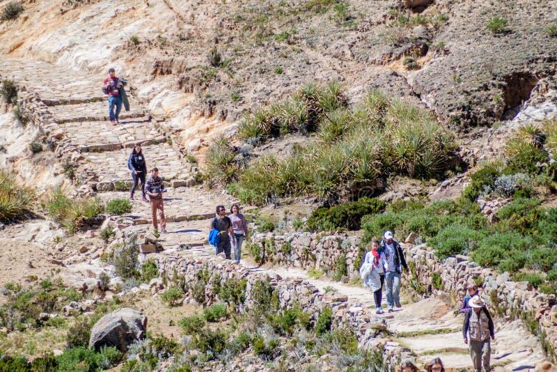 Tourists walk on an ancient inca trail. ISLA DEL SOL, BOLIVIA - MAY 12, 2015: Tourists walk on an ancient inca trail at Isla del Sol Island of the Sun in stock photo