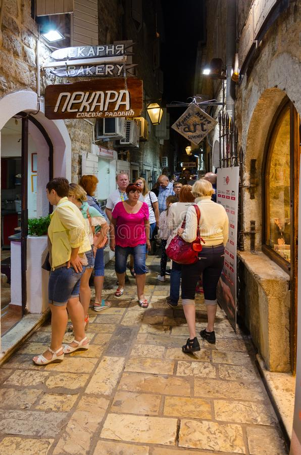 Tourists walk in evening through narrow street of Old Town, Budva, Montenegro. BUDVA, MONTENEGRO - SEPTEMBER 4, 2017: Unknown tourists walk in evening through royalty free stock photos