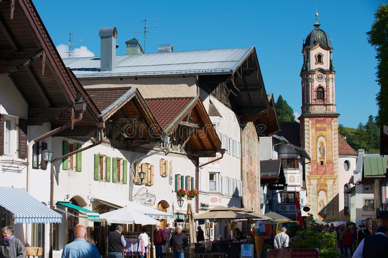 Tourists walk by the street of Mittenwald, Germany. stock photo