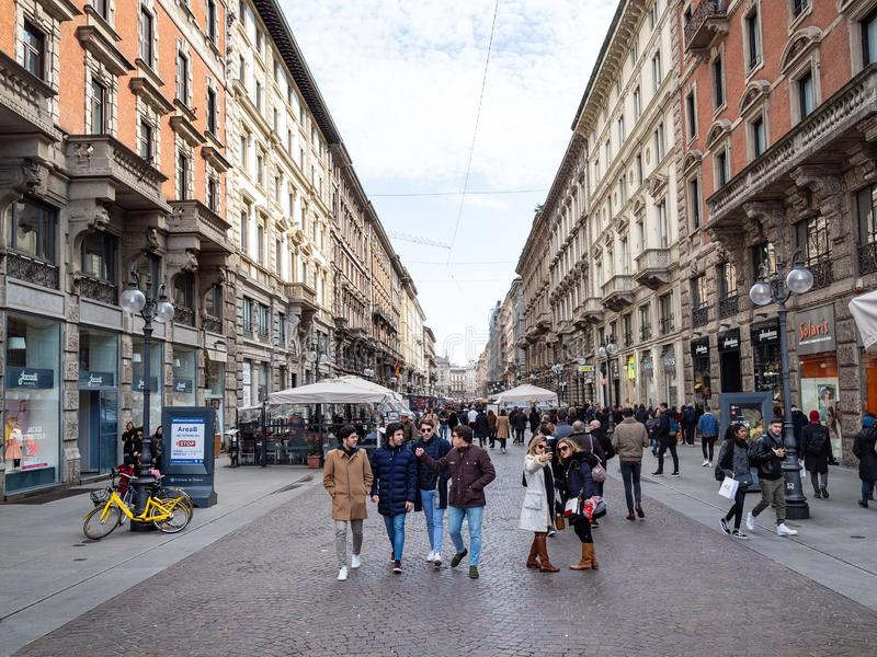 Tourists walk on street Via Dante in Milan city stock photo
