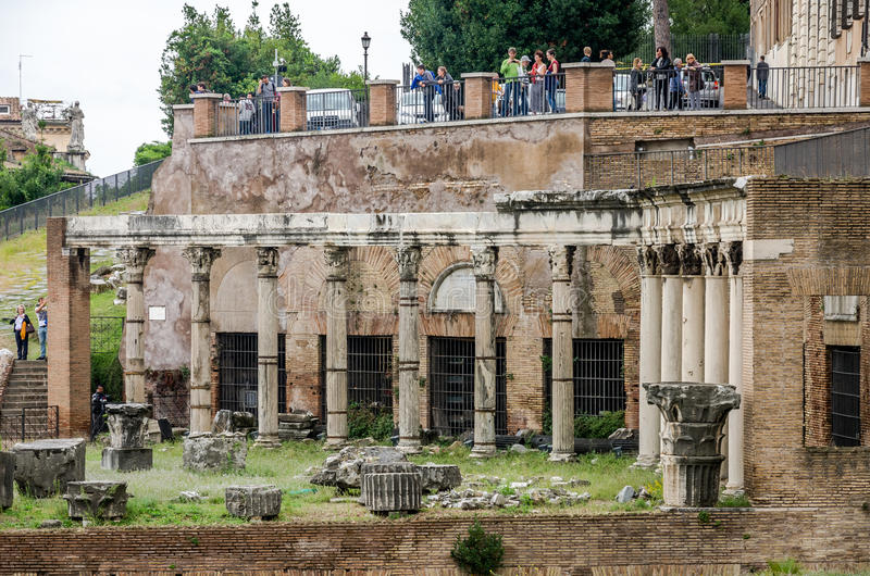 Tourists walk and take pictures in the photo on the tour of the ancient ruins of the ancient imperial capital of the Roman Forum i royalty free stock image