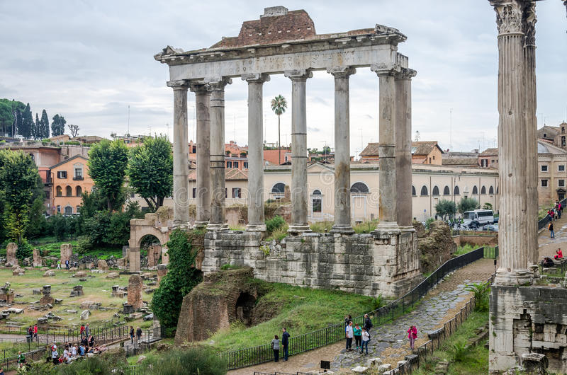 Tourists walk and take pictures in the photo on the tour of the ancient ruins of the ancient imperial capital of the Roman Forum i royalty free stock photos