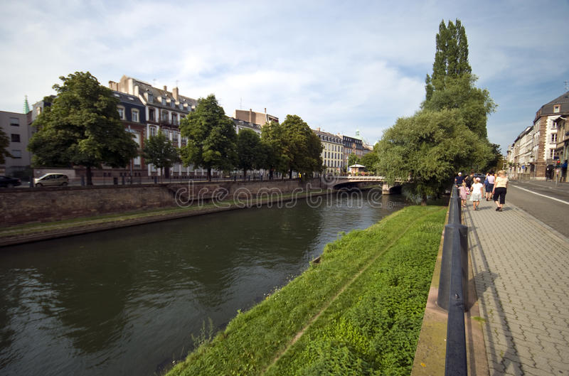 Tourists walking along a river in Strasbourg. A group of tourists walking along a river in the centre of Strasbourg city, France stock photo