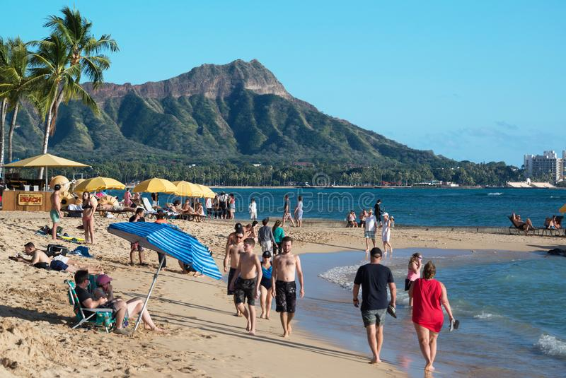 Tourists walking along the shoreline at Waikiki and Diamond Head is a popular and romantic tourist resort in Oahu, Hawaii. royalty free stock photo