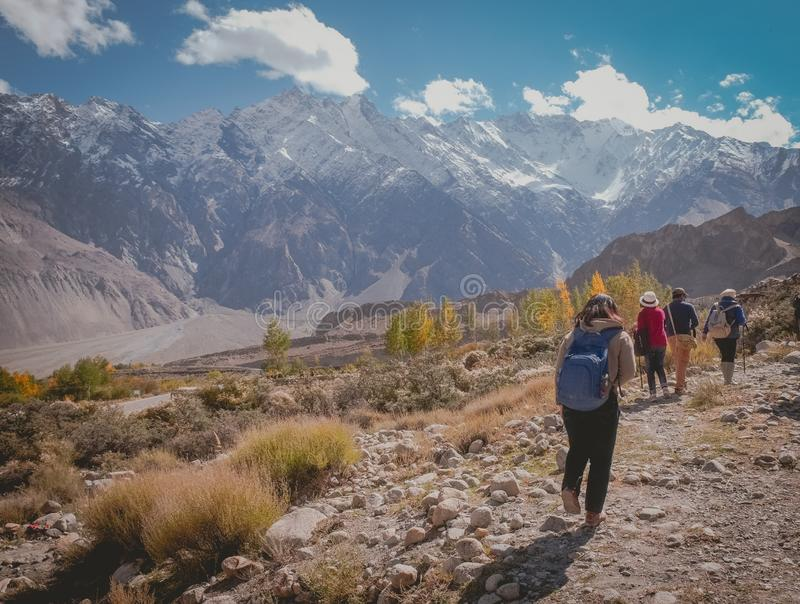 Tourists walking along the track in Passu trekking trail, Pakistan. stock image