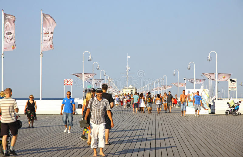 Tourists walking along the wooden pier in Sopot, Poland royalty free stock images