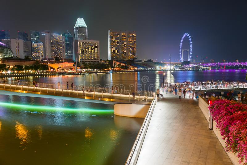 Tourists walking Flyer Singapore embankment. Tourists walking by Singapore embankment, illuminated Flyer, city skyline with modern architecture in background royalty free stock photography