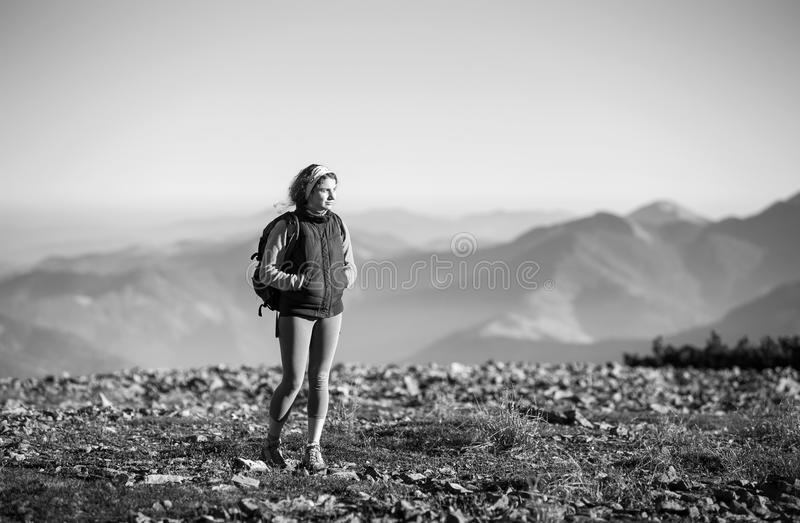Tourists is walking on mountain plato with backpack on. Portrait of young tourist walking on rocky mountains enjoying nature on backpacking trip. Beautiful stock photo
