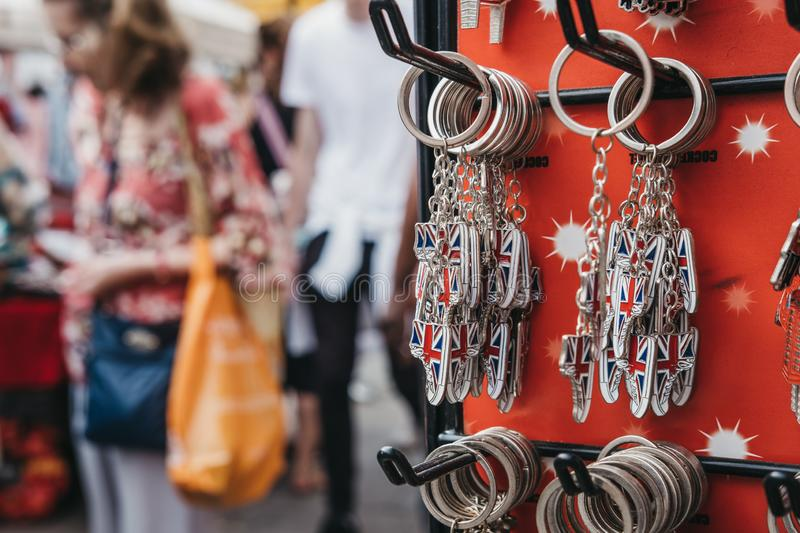 Tourists walking past a stand with souvenir key chain on sale at royalty free stock images