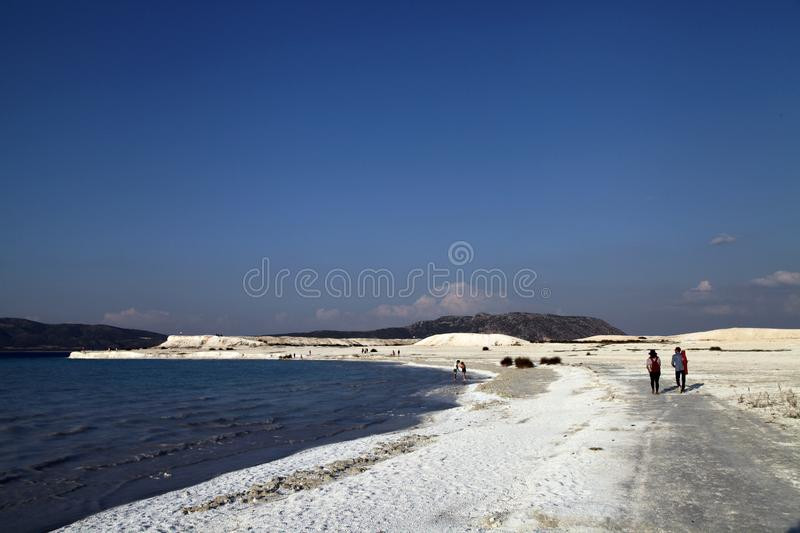 Tourists are walking on Salda Lake beach. Burdur, Turkey - July 22, 2017; Lake Salda is a mid-size crater lake in Burdur, Turkey. Salda beach is a very popular royalty free stock photos