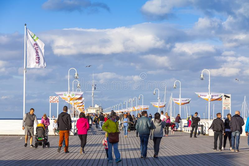 Tourists walking on a Sopot Pier Molo in the city of Sopot, Poland. Sopot, Poland - July 31, 2015: Tourists walking on a pier Molo in Sopot city, Poland. Built stock image