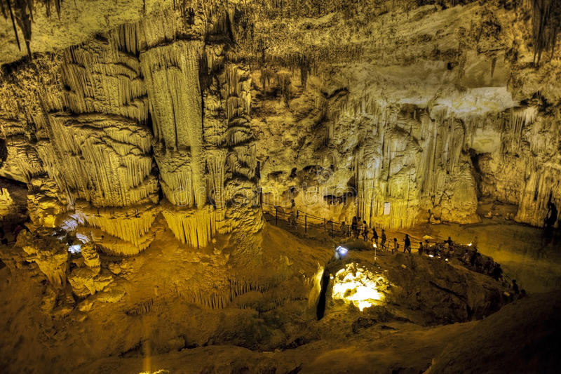 Tourists Walking On Stalactites Cave Looking Infernal Stock Image